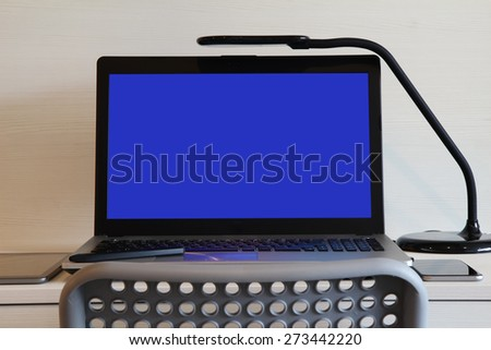 blank blue screen laptop computer with table lamp is on wooden desk as workplace concept - stock photo