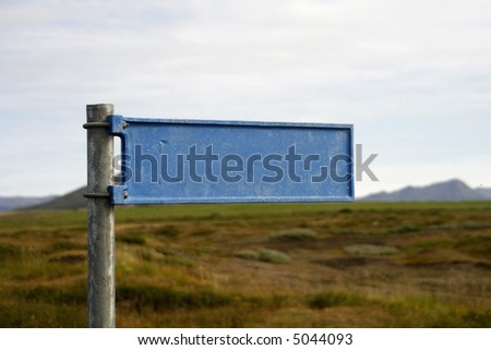 Blank blue signpost. Blue sign in focus hay in background unfocused