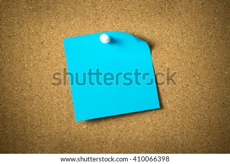 Blank blue sticky note pinned on corkboard - stock photo