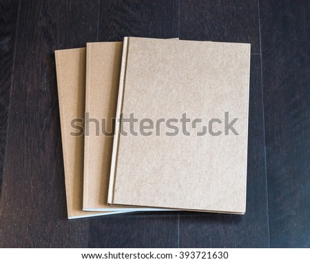 Blank book catalog magazines brochure note cover template w/ recycle brown color paper texture on dark wood table wooden floor background: Eco friendly empty note book page on timber backdrop for text - stock photo