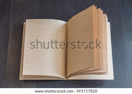 Blank book catalog magazines brochure note template w/ recycle brown paper texture, brown color wood table/ wooden floor background: Eco friendly empty mockup note page on timber backdrop for text - stock photo