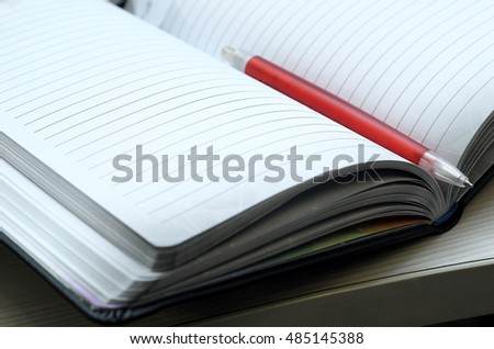 Blank book page with pen on top.