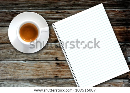 Blank book with coffee and photo frame on wooden background