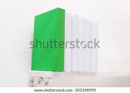 Blank books and green one on shelf on white wallpaper background - stock photo