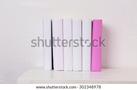 Blank books and pink one on shelf on white wallpaper background - stock photo