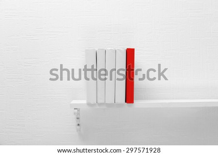 Blank books and red one on shelf on white wallpaper background - stock photo