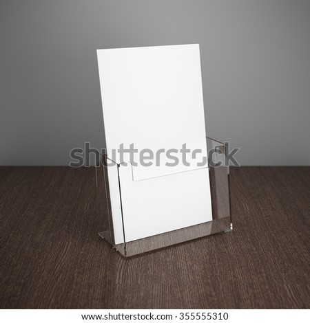 Blank brochure with glass holder on wooden table - stock photo