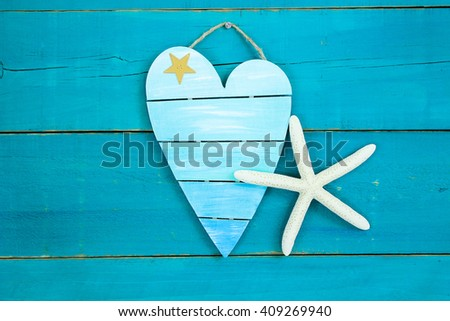Blank broken heart sign with starfish hanging  on antique rustic teal blue wood background; holiday beach sign with metal star - stock photo