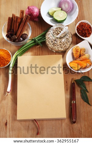 blank brown cover book with spices on a wooden surface