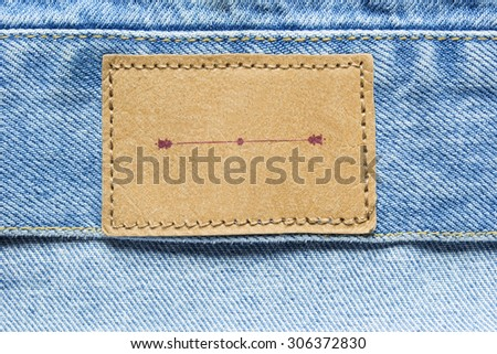 Blank brown label on blue denim as a background