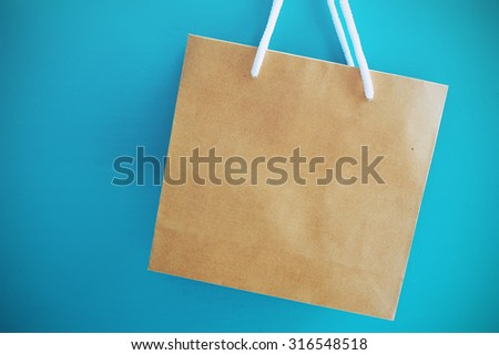 Blank brown shopping bag on blue background.  - stock photo