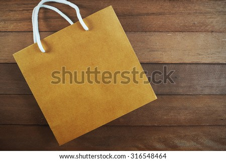 Blank brown shopping bag on wooden background.
