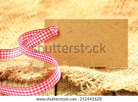 Blank brown tag with copyspace tied with a fresh red and white rustic ribbon on a piece of coarse woven hessian fabric for a natural country background - stock photo