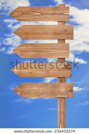Blank brown wooden signpost, arrows against blue sky. Add your own text to the arrows - stock photo