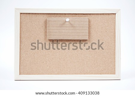 blank brown writing board with a white pin and a small brown piece of cardboard on it.  - stock photo