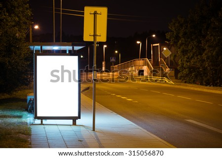 Blank bus stop advertising billboard in the city at night. - stock photo