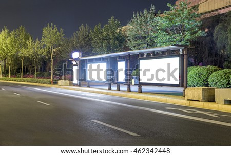 Blank bus stop advertising billboard in the city at night