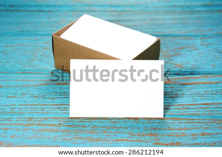 Blank business card with brown paper box on wood desk - stock photo