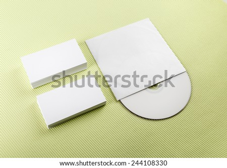 Blank business cards and compact disk on a green background. Template for ID - stock photo