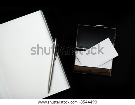 Blank business cards and notebook on dark background