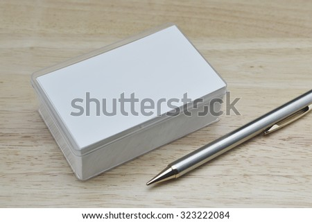 Blank business cards and pencil on wooden office table