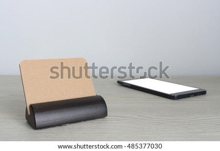 Blank business cards and smartphone on wooden office table with copy space
