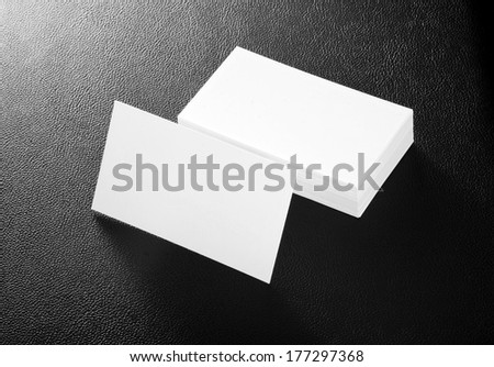 blank business cards on a black leather background - stock photo