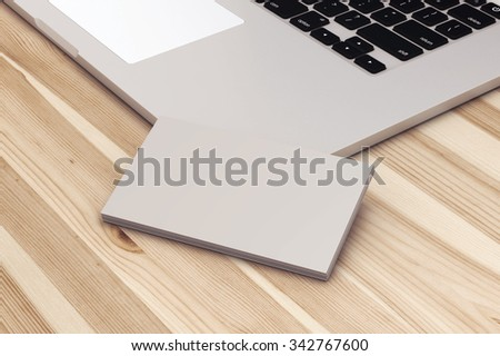 Blank business cards with laptop on wooden office table. - stock photo
