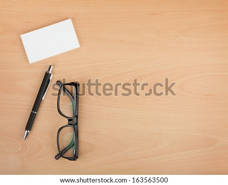 Blank business cards with pen and glasses on wooden office table with copy space - stock photo