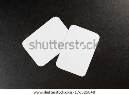 blank business cards with rounded corners on a black leather background - stock photo