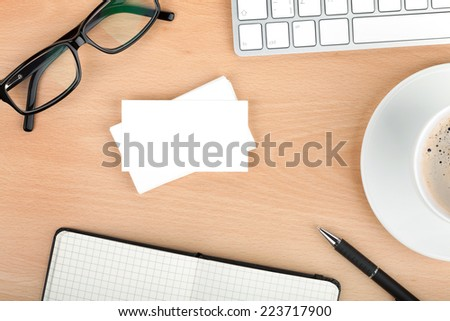 Blank business cards with supplies and coffee cup on wooden office table - stock photo