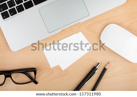 Blank business cards with supplies on wooden office table - stock photo