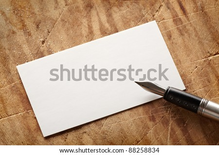 Blank business (visit) card on old wooden table with vintage fountain pen. - stock photo