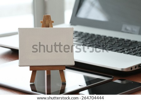 blank canvas and wooden easel on laptop computer as concept - stock photo