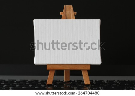 blank canvas and wooden easel on laptop computer as concept