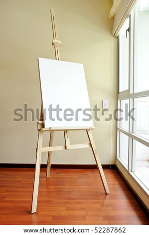Blank canvas on a wooden tripod in the studio - stock photo