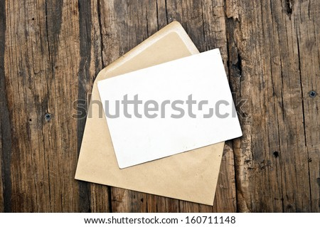 Blank card and envelope on old wooden background - stock photo