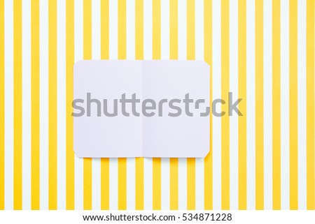 Blank card paper on yellow striped background.