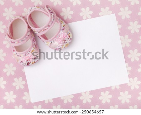 Blank card with baby girl shoes on a pastel pink floral background.