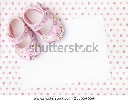 Blank card with baby girl shoes on a pastel pink spotted background. - stock photo