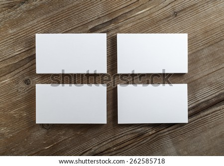 Blank cardboard business cards on a dark wooden table. Template for ID. Top view. on a dark wooden table. Template for ID. Top view. - stock photo
