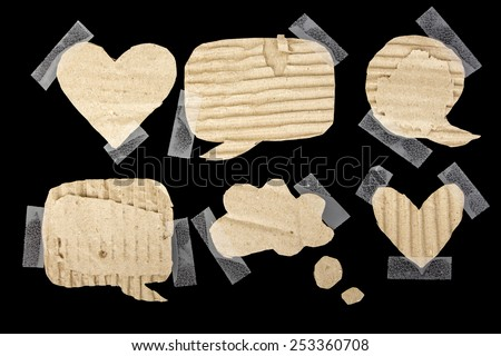Blank cardboard paper speech bubbles, stuck with scotch tape isolated on black - stock photo