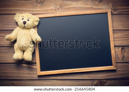 blank chalkboard and teddy bear on wooden table - stock photo