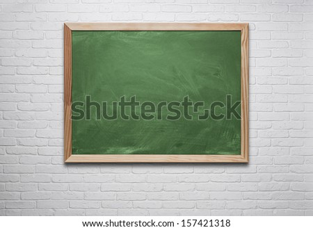 Blank chalkboard, blackboard hanging on the white brick wall with copy space - stock photo