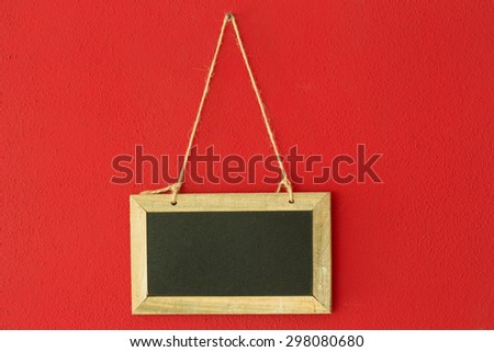 blank chalkboard hanging on the red wall - stock photo