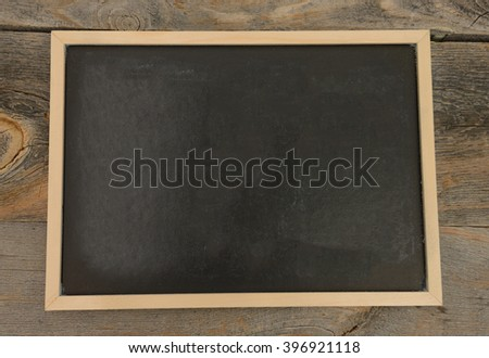 Blank chalkboard on a rustic background - stock photo