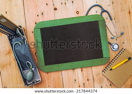 Blank chalkboard on background, with sphygmomanometer and stethoscope - stock photo