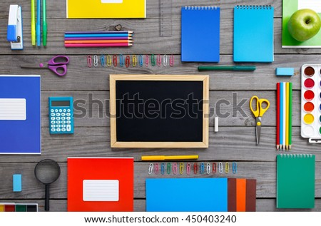 Blank chalkboard with school supplies on a wooden table, top view. Back to school - stock photo