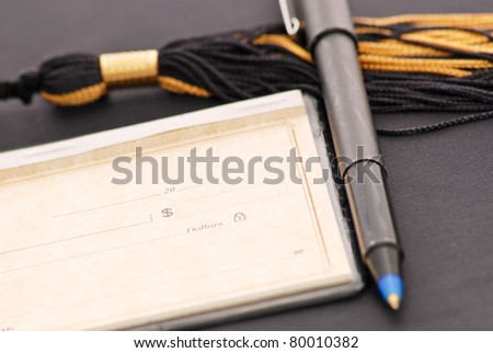 Blank Check with Pen on Graduation Tassel - stock photo