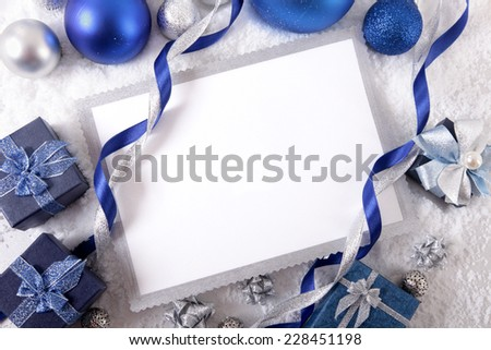 Blank Christmas card or invitation surrounded by ribbons and decorations. Space for copy. - stock photo